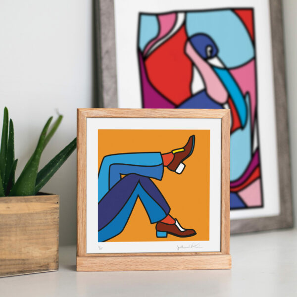 Image of a wooden square frame with an illustration of two men feet in a relaxing pose. Next to the frame is a plant and behind the frame is in the distance another framed illustration.