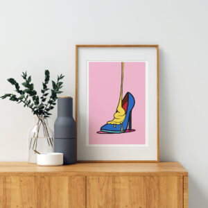 Framed colorful shoe art print standing on a dresser - Solleveld & Toim