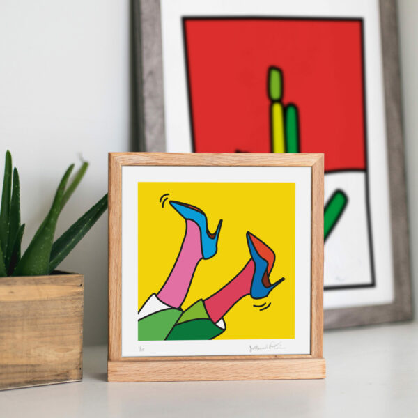 Image of a wooden square frame with an illustration of two feet with heels up in the air. Next to the frame is a plant and behind the frame is in the distance another framed illustration.