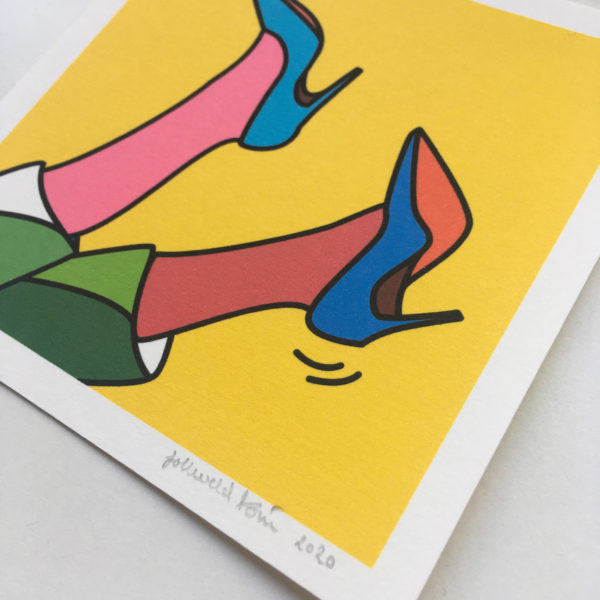 Close-up of a mini art print that shows an illustration of two feet with heels up in the air.